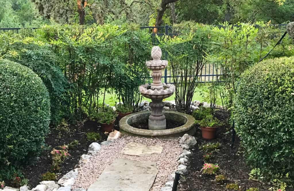 Nandina growing in landscaping around a water fountain and bird bath.